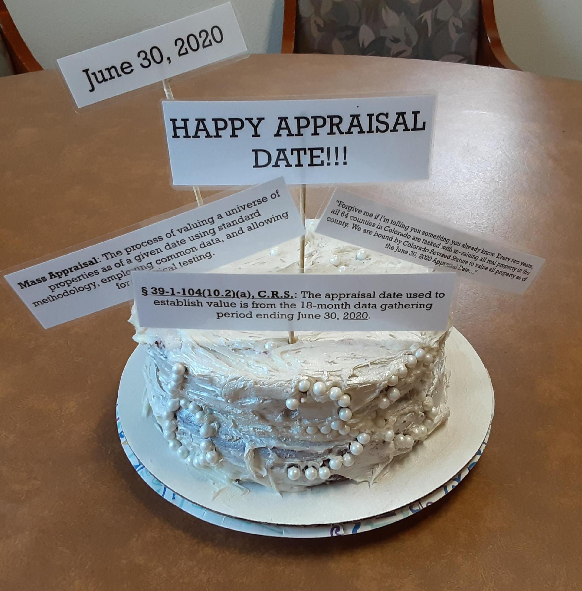 A cake with white frosting and small signs related to June 30, 2020, the County Appraisal Date